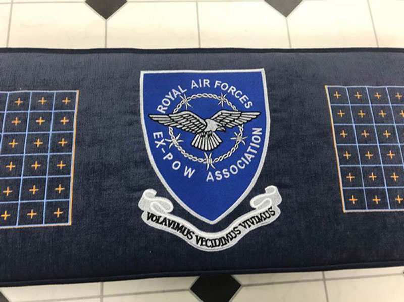 A details showing the embroidered crest of the Royal Air Forces Ex POW Association on the bespoke church kneeler